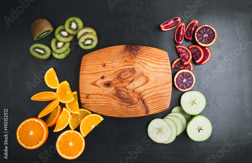 Fresh oranges, kiwi, and apples on dark gray surface, top view with free space for text