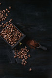 Fototapety Roasted coffee beans and grind coffee in wood box with scoop over black wooden burnt background. Top view with space.