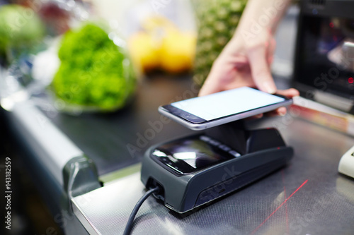 Modern consumer keeping smartphone over cashier-machine to pay for purchase in supermarket
