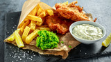 British Traditional Fish and chips with mashed peas, tartar sauce on crumpled paper. - 143185903