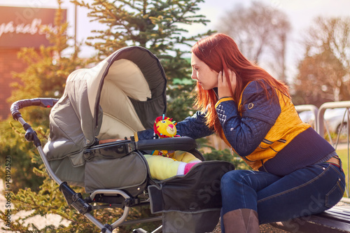 Poster Woman with red hair looking at the baby in carriage