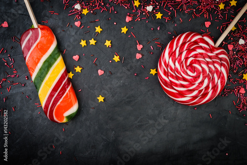 Colorful  spiral lollipops with sprinkles over dark stone or concrete  background Poster