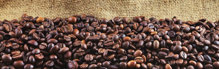 Fried coffee beans on jute. Panorama. © fydorov