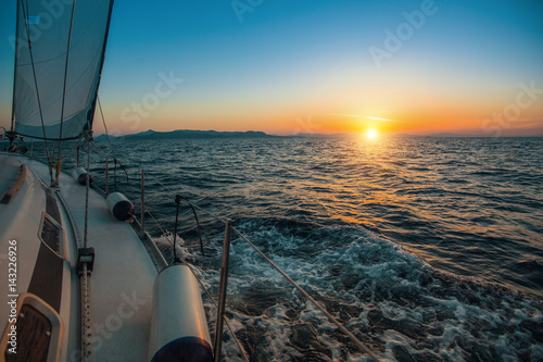 Sailboat with sails set to Sea at full speed at amazing sunset. Luxury cruise yacht.  .