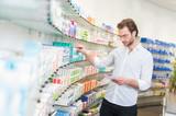 Apotheker sucht Medikamente aus einem Regal