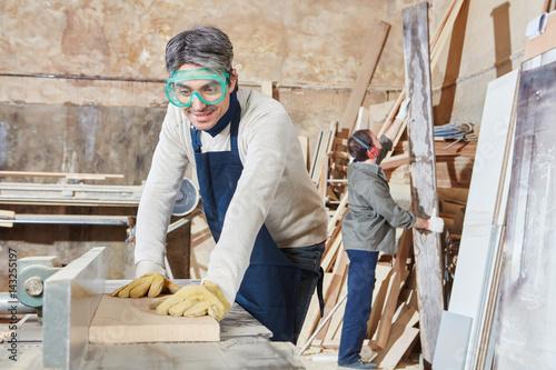 Poster Schreiner hobelt Holz in Schreinerei