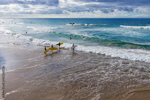 Fotobehang Canarische Eilanden Spain, Canary Islands, Fuerteventura, La Pared. Group of boys goes surfing.