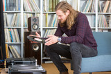long haired man putting a vinyl on the turntable - 143272996