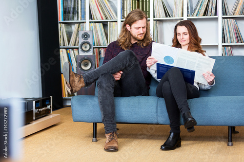 a couple taking a vinyl out of the cover to play