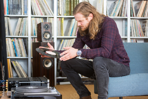 Poster long haired man putting a vinyl on the turntable