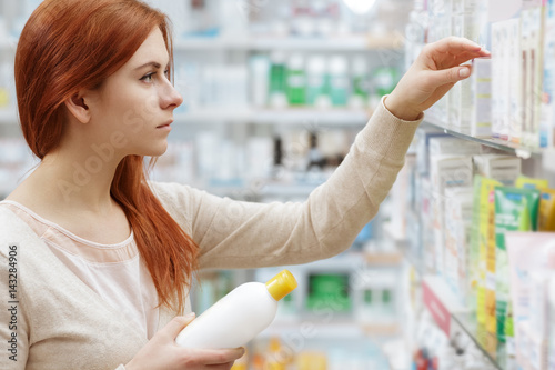 Tuinposter Apotheek So many brands. Shot of an attractive young female concentrated on choosing medicine on the pharmacy shelf.