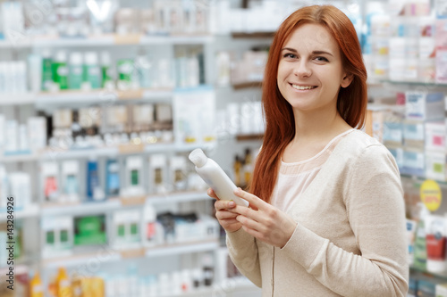 Foto op Aluminium Apotheek Happy to decide. Portrait of a happy pharmacy client holding a medication product looking to the camera smiling.