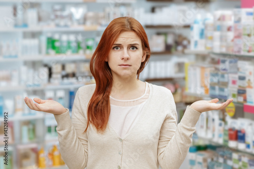 Need help. Portrait of a young frustrated woman looking to the camera at the local drugstore.