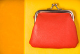 Orange purse on the bright yellow background top view