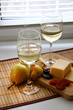 Glasses with white wine and cheese with fruit..