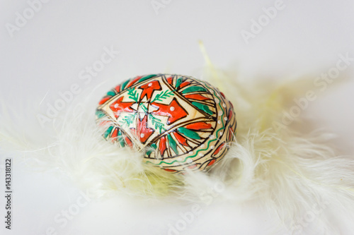 Closeup of decorated wooden Easter egg placed on a nest of feathers. Concept Easter.