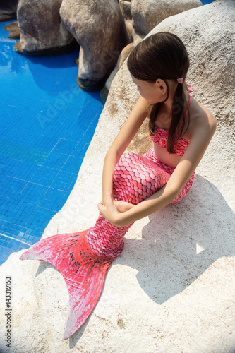 Mermaid girl with pink tail on rock at poolside Poster