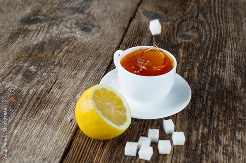 sweet cup of fruit tea with lemon and sugar on a wooden background Poster