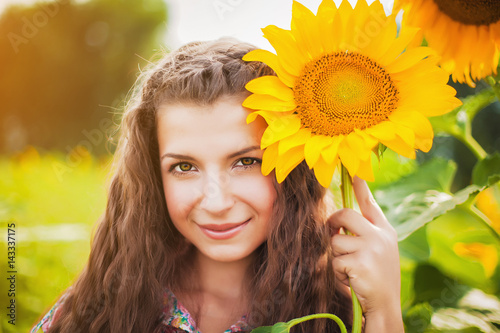 Beautiful young woman and sunflowers