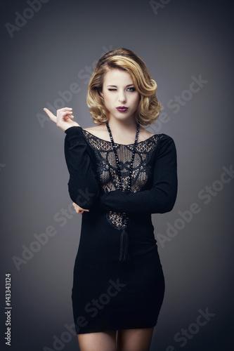 Plakat Jeune femme en robe noire, de face, fait un clin d'oeil