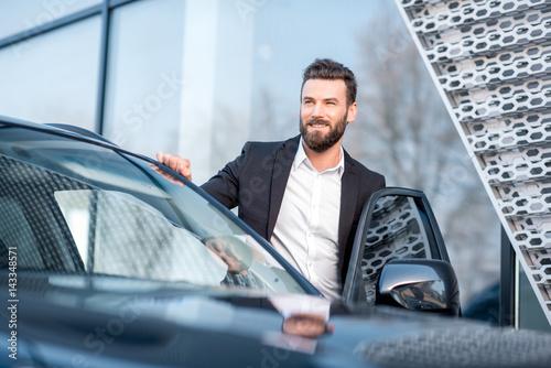 Portrait of a handsome businessman standing near the car outdoors near the modern building facade