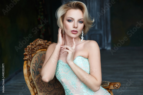 Plakat Beautiful blond woman in a cocktail dress is sitting in a posh armchair