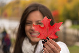 Beautiful smiling girl holding red maple leaf (Canada´s symbol) in a park in autumn, Focus at the red maple leaf, girl blurred.
