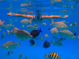 Man with black hair has been snorkeling on the island of San Andres in the Caribbean sea. He feeds the fish under water in clear blue sea. - 143367167