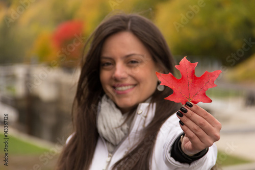 Foto op Plexiglas Canada Beautiful smiling girl holding red maple leaf (Canada´s symbol) in a park in autumn, Focus at the red maple leaf, girl blurred.