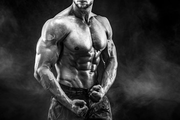 Strong bodybuilder with six pack. Man with perfect abs, shoulders,biceps, triceps and chest, personal fitness trainer flexing his muscles in smoke © zamuruev