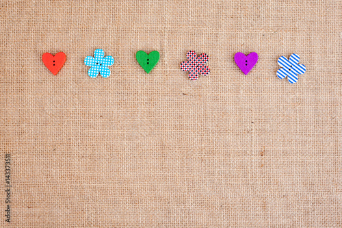 Poster background - natural color burlap hessian with flower and heart shape buttons