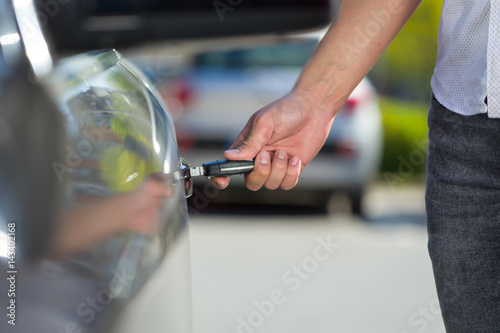 Poster man hand open the car door with alarm security key