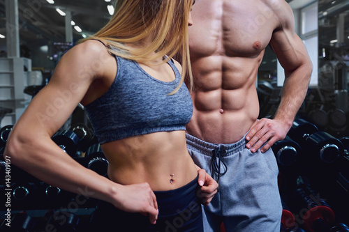 Strong man and a woman are posing with beautiful bodies. Sports couple in the gym.