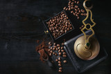 Fototapety Roasted coffee beans and grind coffee in wood box with vintage coffee grinder and scoop over black wooden burnt background. Top view with space.