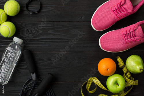 Athlete's set with female clothing and bottle of water on dark background