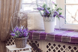 Lavender flowers in white pots and and wicker baskets stands on the windowsill. Horizontal - 143424913