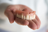 closeup of womans hand holding a teeth denture - 143425394