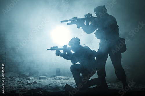 Black silhouettes of pair of soldiers in the smoke haze moving in battle operation