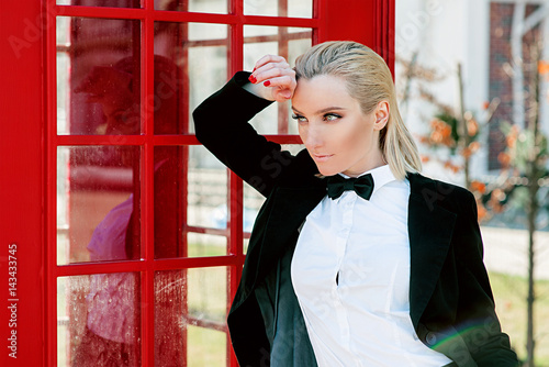 Portrait of stylish beautiful blonde woman in man black suit near red telephone  Poster