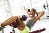 Young woman exercise abs in the gym on the bench