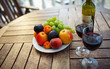 red wine, fruit and wine on the table prepared for a romantic date
