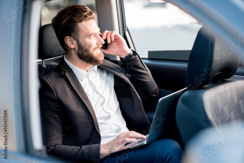 Handsome businessman talking with phone sitting on the backseat of the car