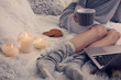 Cozy evening , warm woolen socks, soft blanket, candles. Woman relaxing at home,drinking cacao, using laptop. Comfy lifestyle.