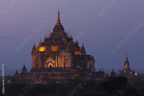 Huge temple lit up in Bagan after sunset  Poster
