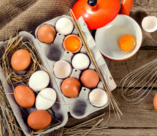 Chicken eggs in egg box on rustic wooden background.
