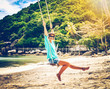 Happy young woman in a hat on a swing on the shore of a warm tropical sea. Travel joy freedom concept