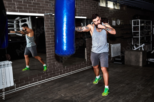 Staande foto Young bearded tattooed man hits a punching bag in the gym. Full body length portrait.