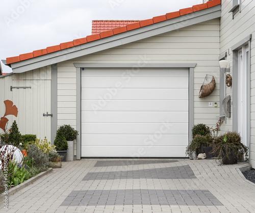 Papiers peints Brick wall Garage mit einem weißen Tor