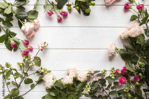 Border of  various roses on white wooden background