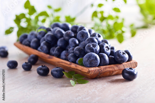 Fresh juicy blueberries with green leaves on a kitchen table .